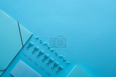 Photo pour Flat lay of paper binder and various stationery isolated on blue with copy space - image libre de droit