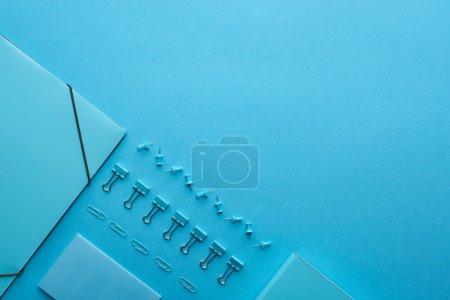 Flache Lage aus Papierordner und diverse Schreibwaren isoliert auf blau mit Kopierraum