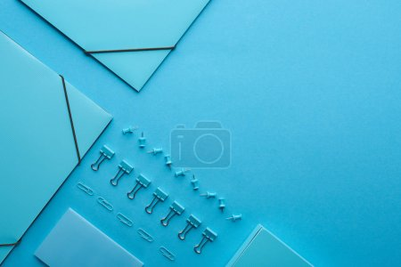 Photo for Flat lay of paper binders and arranged stationery isolated on blue with copy space - Royalty Free Image