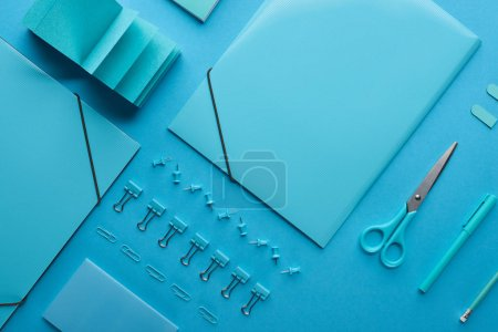 Photo for Flat lay of paper binders and various arranged stationery isolated on blue - Royalty Free Image