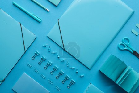 Photo for Flat lay of paper binders, paper clips and various stationery isolated on blue - Royalty Free Image