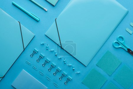 Photo for Flat lay of paper binders and organized stationery isolated on blue - Royalty Free Image