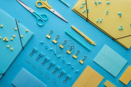 Photo pour Vue supérieure de la papeterie colorée diverse d'isolement sur le bleu - image libre de droit
