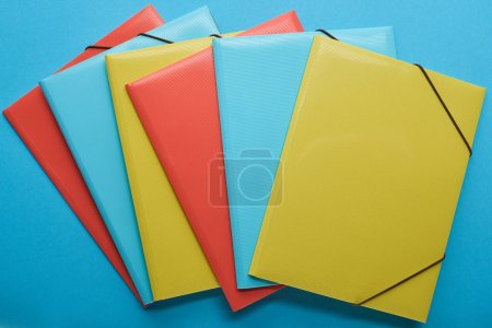 Photo for Top view of multicolored office paper binders on blue - Royalty Free Image
