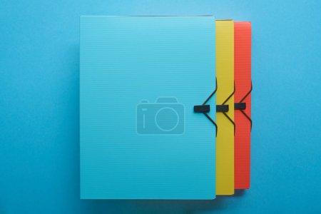 Foto de Vista superior de los aglutinantes de papel multicolor en la fila en azul - Imagen libre de derechos