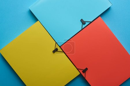 Photo for Top view of arranged colorful paper folders on blue - Royalty Free Image