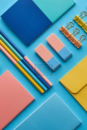 Photo for Top view of notebooks and colorful stationery isolated on blue - Royalty Free Image