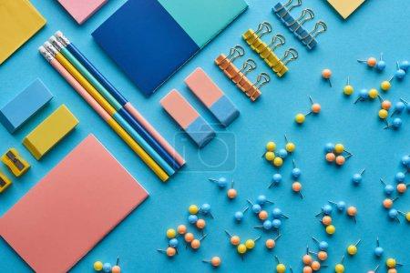 Photo pour Vue du haut des cahiers et de la papeterie colorée diverse d'isolement sur le bleu - image libre de droit