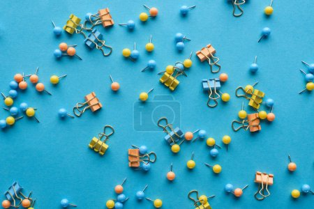 top view of colorful scattered push pins and paper clips isolated on blue