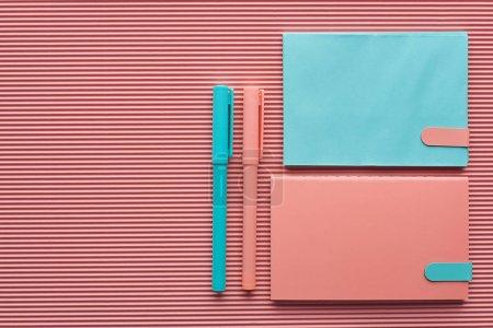 Photo pour Vue du dessus des stylos et carnets disposés sur rose texturé avec espace de copie - image libre de droit