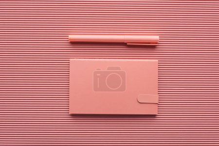Photo for Top view of pen and notepad on textured pink - Royalty Free Image