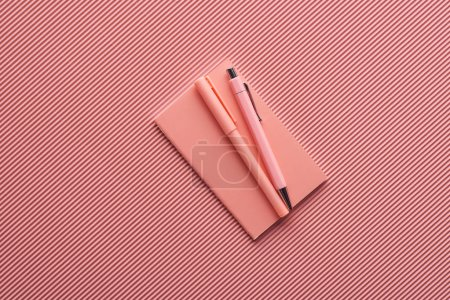 Photo pour Minimalistic background with pens and notebook on textured pink - image libre de droit