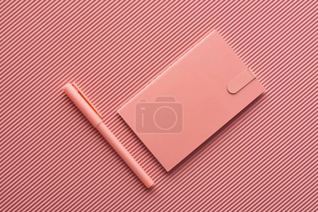 Photo for Top view of pen and notebook on textured pink - Royalty Free Image