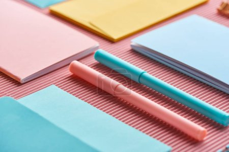 Photo for Close up of colorful pens and notebooks on pink - Royalty Free Image