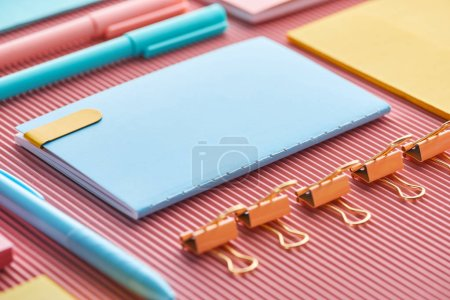 Photo for Selective focus of notebook, paper clips and colorful stationery supplies on pink - Royalty Free Image