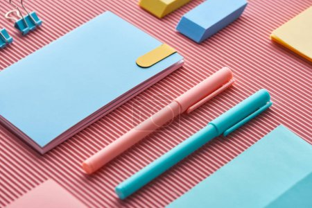 Photo pour Stylos colorés, cahiers et gommes à effacer sur rose - image libre de droit