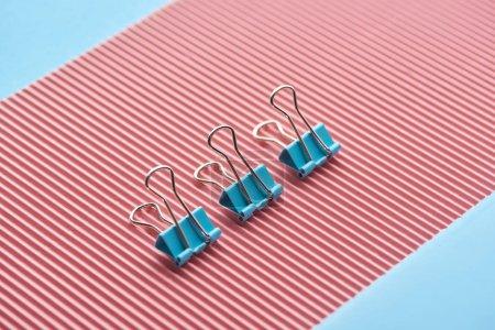 Photo pour Trombones métalliques sur papier rose texturé isolé sur bleu - image libre de droit