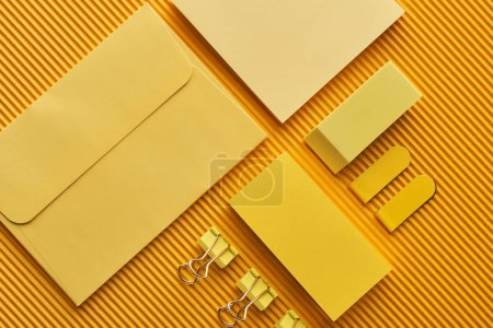Photo for Top view of arranged office stationery supplies on yellow - Royalty Free Image