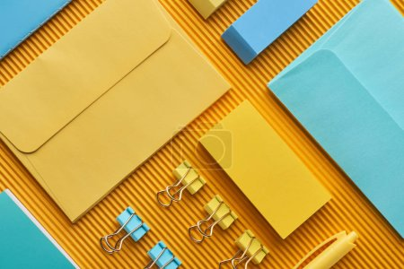 Photo for Flat lay of multicolored arranged office stationery supplies on yellow - Royalty Free Image