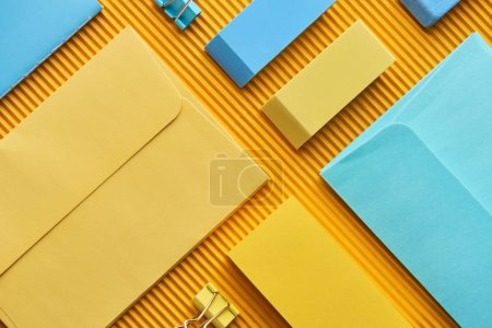 Photo for Top view of sticky notes, envelopes and erasers on yellow - Royalty Free Image
