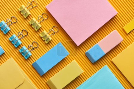 Photo for Flat lay of colorful arranged stationery supplies on yellow - Royalty Free Image