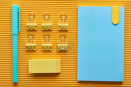 Photo for Top view of pen, notebook and colorful arranged office stationery supplies on yellow - Royalty Free Image