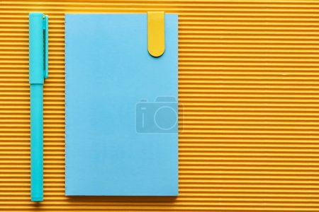 Photo for Top view of blue pen and notebook on yellow with copy space - Royalty Free Image