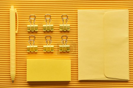 Photo for Top view of pen, paper clips and arranged office stationery supplies on yellow - Royalty Free Image