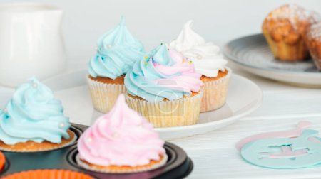 Photo for Delicious cupcakes decorated with colorful frosting on plate isolated on grey - Royalty Free Image