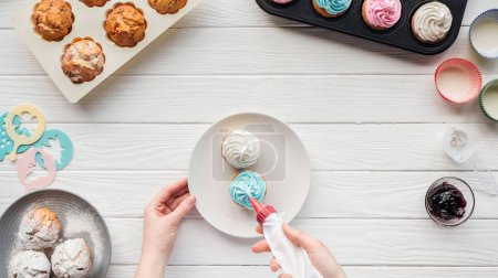 Photo for Partial view of woman decorating cupcakes with icing bag on table with cupcake trays - Royalty Free Image