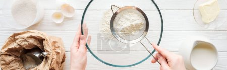 Photo for Panoramic shot of woman sieving flour in bowl on table with ingredients - Royalty Free Image