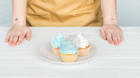 Photo for Cropped view of woman near plate with delicious cupcakes on white table on grey - Royalty Free Image