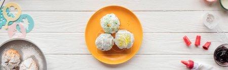 Photo pour Plan panoramique de délicieux cupcakes et outils de cuisson sur table en bois - image libre de droit