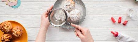 Photo pour Coup panoramique de la femme décorant des petits gâteaux avec le sucre en poudre sur la table blanche - image libre de droit