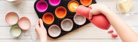 Photo pour Plan panoramique de la femme versant la pâte liquide dans la casserole de cupcake sur la table - image libre de droit