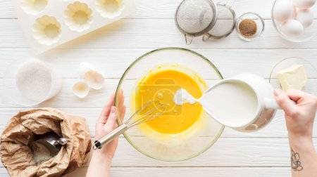 Cropped view of woman pouring milk in liquid dough on table with ingredients