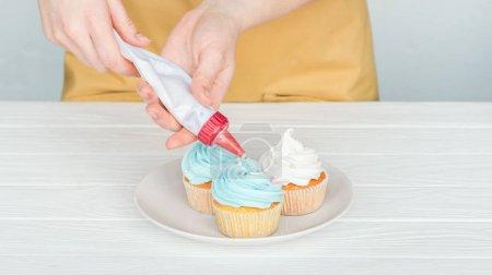 abgeschnittene Ansicht einer Frau, die Cupcakes mit Zuckerguss verziert