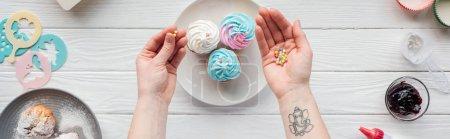 Photo pour Tir panoramique de la femme retenant saupoudre tout en décorant des petits gâteaux sur la table blanche - image libre de droit