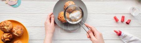 Photo pour Coup panoramique de la femme décorant des petits gâteaux avec le sucre en poudre et le tamis sur la table blanche - image libre de droit