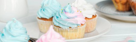 Photo for Panoramic shot of colorful cupcakes with frosting on plate - Royalty Free Image