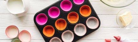 Photo pour Moule panoramique de muffin de projectile, beurre, formes de papier et sac de glaçage sur la table - image libre de droit