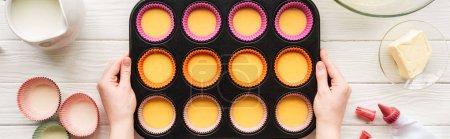 Photo pour Tir panoramique de la femme retenant le moule de muffin avec la pâte liquide sur la table avec des ingrédients - image libre de droit