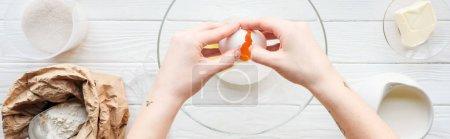 Photo pour Plan panoramique de femme craquant oeuf dans un bol tout en cuisinant sur la table - image libre de droit
