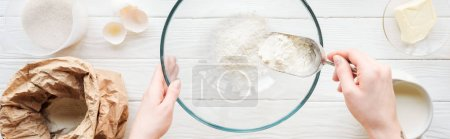 Photo for Panoramic shot of woman with scoop putting flour in bowl while cooking on table - Royalty Free Image