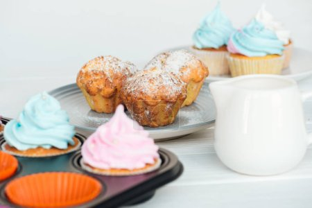 Photo for Delicious muffins and cupcakes with colorful frosting isolated on grey - Royalty Free Image