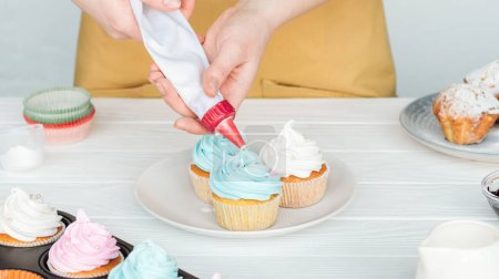 Photo for Partial view of woman decorating cupcakes with icing bag - Royalty Free Image