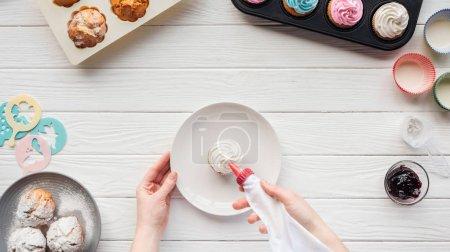 Photo pour Vue cultivée de gâteau de décoration de femme avec le sac de glaçage sur la table avec des plateaux de gâteau - image libre de droit