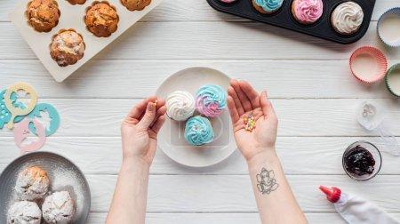 Photo pour Cropped de la femme retenant saupoudre tout en décorant des petits gâteaux sur la table blanche - image libre de droit