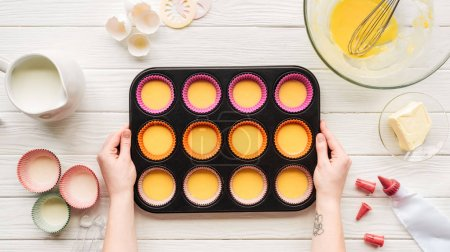 Photo for Cropped view of woman holding muffin mold with liquid dough on table with ingredients - Royalty Free Image