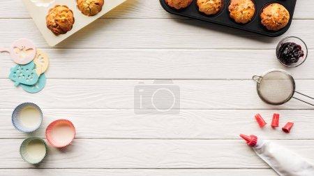 Photo pour Vue supérieure des muffins délicieux et des outils de cuisson sur la table en bois avec l'espace de copie - image libre de droit